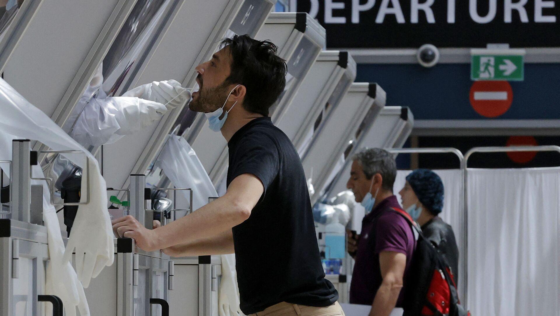 Медик берет мазок у путешественника в будке для экспресс-тестирования COVID-19 в израильском аэропорту Бен-Гурион - Sputnik Беларусь, 1920, 08.04.2021