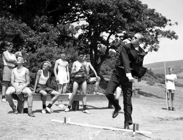 Принц Филипп, герцог Эдинбургский, бросает копье во время посещения морской школы в Уэльсе в 1949 году - Sputnik Беларусь