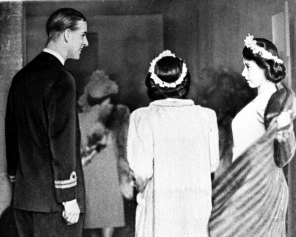 Принц Филипп Греческий помогает принцессе Елизавете (справа) и принцессе Маргарет с пальто в аббатстве Ромси, Хэмпшир, 23 декабря 1946 года, где состояласьна свадьба Патрисии Маунтбеттен - Sputnik Беларусь