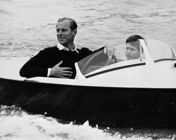 Принц Филипп с сыном принцем Чарльзом за штурвалом своего скоростного катера во время путешествия по реке Медине - Sputnik Беларусь