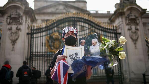 Скорбящая держит цветы и фотографии королевы Великобритании Елизаветы II и ее мужа принца Филиппа возле Букингемского дворца после смерти принца Филиппа - Sputnik Беларусь