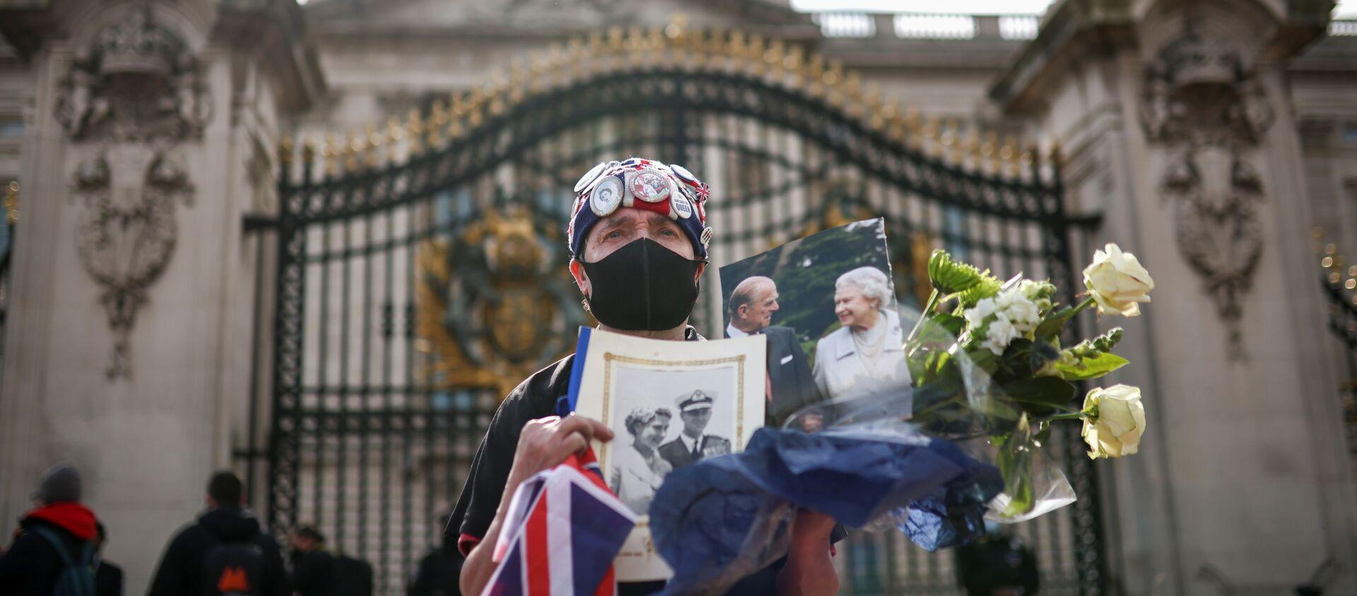 Скорбящая держит цветы и фотографии королевы Великобритании Елизаветы II и ее мужа принца Филиппа возле Букингемского дворца после смерти принца Филиппа - Sputnik Беларусь, 1920, 09.04.2021