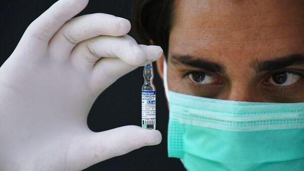 Медицинский работник держит в руках ампулу с российским препаратом от коронавирусной инфекции Гам-Ковид-Вак (Спутник V) - Sputnik Беларусь