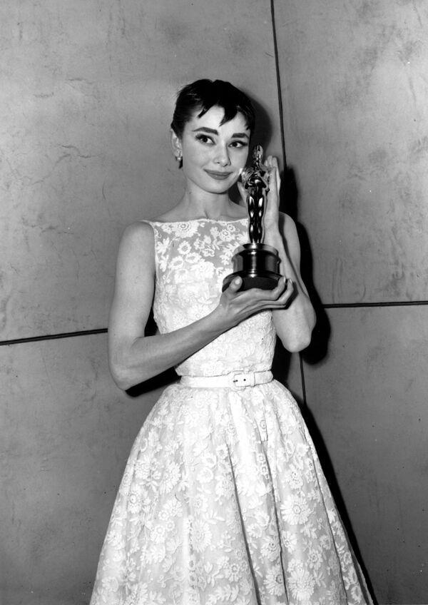 Одри Хепберн в платье Givenchy с Оскаром за роль в фильме Римские каникулы, 1954 год. В финальных кадрах ленты актриса появляется в подобном платье, дизайнер сделал для нее такое же - кружевное и изящное. - Sputnik Беларусь