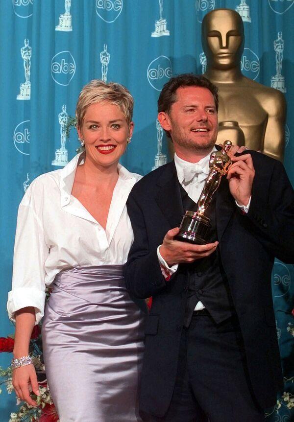 Актриса Шэрон Стоун и режиссер Майк Ван Дим на 70-й церемонии вручения премии Оскар, 1998 год. Только такая женщина как Шэрон с безупречным вкусом могла удивить модных критиков. Она появилась на красной дорожке в стиле casual — к лиловой юбке от Веры Вонг она подобрала простую белую рубашку Gap, которую, по ее собственному признанию, позаимствовала у своего тогдашнего мужа Фила Бронштейна. - Sputnik Беларусь