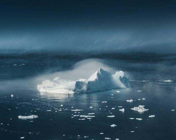 Айсберги выплывают из тумана словно гигантские белые замки на западном побережье Гренландии. Лодка слева от айсберга  дает представление о его масштабе. - Sputnik Беларусь