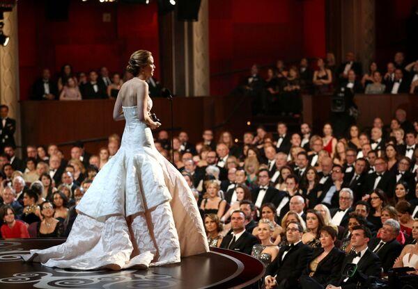 Дженнифер Лоуренс на церемонии вручения премии Оскар, 2013 год. Нежнейшее розовое творение от Christian Dior - самое дорогое платье за всю историю Оскара. И то, что актриса оступилась, поднимаясь в пышном платье на сцену за заветной статуэткой, сделала его только дороже. - Sputnik Беларусь