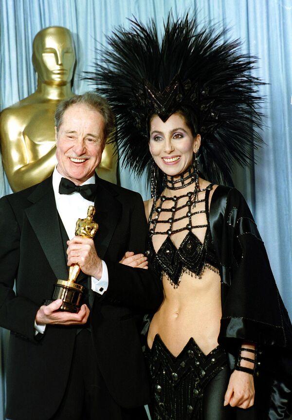 Актриса и певица Шер в творении дизайнера Боба Маки позирует с актером Доном Амече на церемонии вручения премии Оскар в Лос-Анджелесе, 1986 год.  Эпатировав публику в костюме индейца, через два года она явится за своим Оскаром в наряде восточной женщины от этого же дизайнера. - Sputnik Беларусь