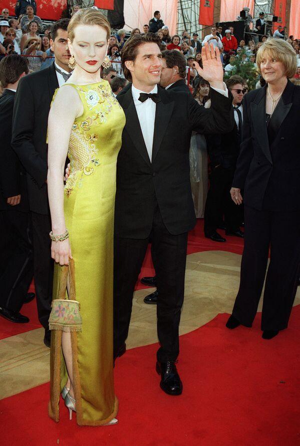 Супруги Том Круз и Николь Кидман на 69-й церемонии вручения премии Оскар. Для 1997 года выход рыжеволосой Николь в сложного зеленого цвета платье с ориентальными мотивами от Christian Dior было совершенно беспрецедентным. Мода красных дорожек тогда предполагала лишь черные футляры и нюдовые наряды из шифона. Автором шедевра был Джон Гальяно, только вступивший на пост креативного директора бренда, а благодаря этому выходу Кидман получивший колоссальную популярность. - Sputnik Беларусь