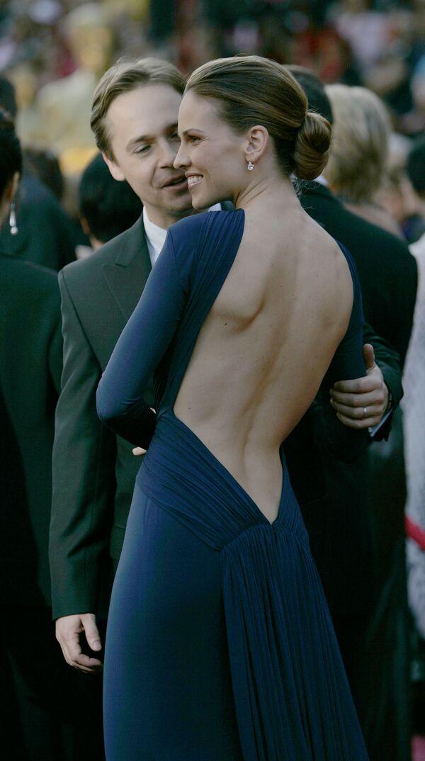 Актриса Хилари Суэнк со своим мужем Чадом Лоу на церемонии вручения премии Оскар, 2005 год. Малышка на миллион - за роль в этом фильме она получила в том году статуэтку. И выглядела сногсшибательно в платье Guy Laroche цвета ночного неба с обнаженной спиной. - Sputnik Беларусь