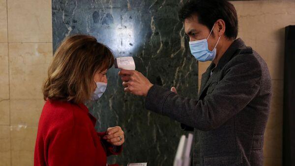 Женщине проверяют температуру перед началом спектакля в Театро Васкелло в день его открытия - Sputnik Беларусь