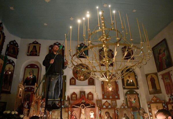 Настоятель церкви Святого Николая Чудотворца отец Сергий зажигает свечи на паникадиле перед пасхальной службой - Sputnik Беларусь