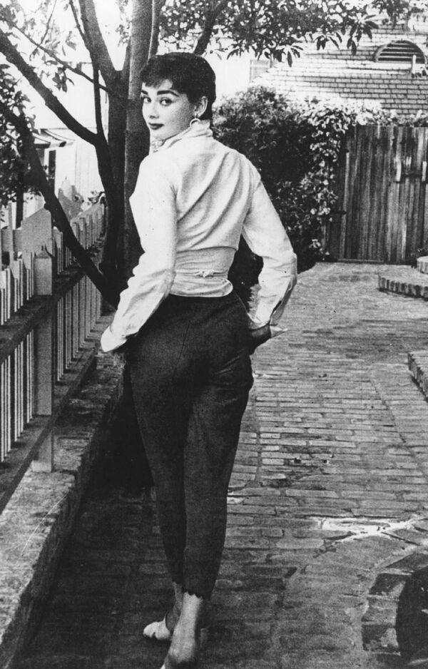 Кинозвезда Одри Хепберн прогуливается перед своей квартирой в Беверли-Хиллз. - Sputnik Беларусь