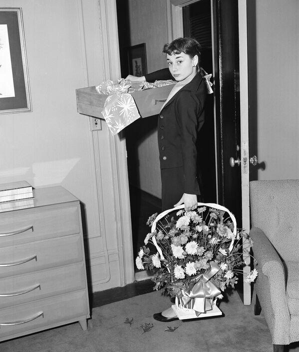 Актриса с цветами от поклонников в своем новом трехкомнатном номере отелея Blackstone в Нью-Йорке. В 1951 году Хепберн исполняла главную партию в Бродвейской постановке Жижи, которая полгода с успехом шла в Нью-Йорке. Одри завоевала Theatre World Award за эту роль.  - Sputnik Беларусь