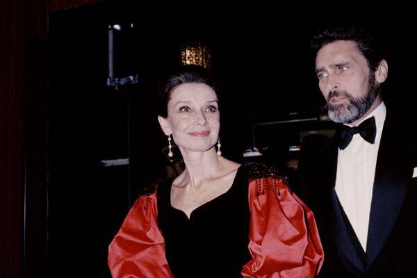 Одри Хепберн и ее спутник голландский актер Роберт Уолдерс на благотворительной вечере по исследованию СПИДа в Париже 25 ноября 1985 года. Они начали встречаться в 1980-м и были вместе вплоть до ее смерти 20 января 1993 года. Актриса скончалась на 64-м году жизни после операции по удалению опухоли.  - Sputnik Беларусь