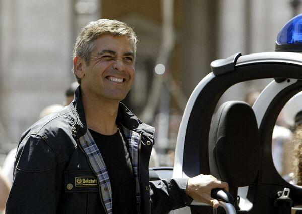 Джордж Клуни позирует на площади Кампидольо в Риме 24 июня 2003 года рядом с одним из десяти скутеров BMW C1, переданных в дар мэрии Рима и Фонду лечения сердечных заболеваний. - Sputnik Беларусь