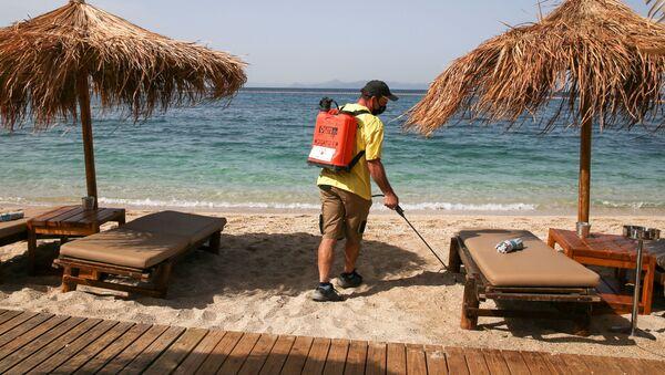 Мужчина дезинфицирует лежаки на пляже в Греции - Sputnik Беларусь