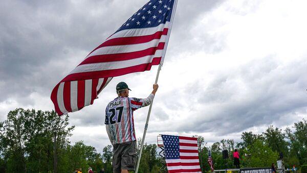 Участник размахивает американским флагом во время митинга по внесению поправок ко 2-й поправке - Sputnik Беларусь