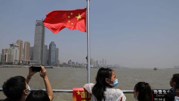 Люди стоят возле китайского национального флага на лодке, пересекающей реку Янцзы, во время праздника Дня труда в Ухане - Sputnik Беларусь