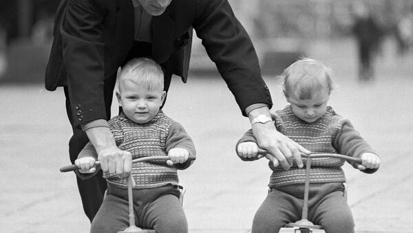 Отец учит детей-близнецов кататься на трехколесных велосипедах, 1968 год - Sputnik Беларусь