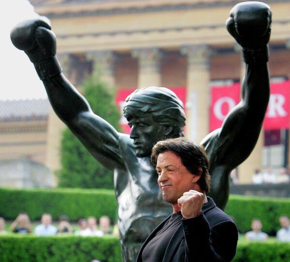 """Тем не менее он обеспечил себе триумфальное возвращение с фильмом """"Рокки Бальбоа"""". Сюжет картины о чемпионе, который отошел от дел, перекликается с биографией самого актера. На фото Сталлоне рядом со статуей боксера у ступеней Художественного музея Филадельфии. По длинной лестнице перед входом в музей ежедневно бегают сотни туристов, повторяющих знаменитые тренировки Бальбоа. - Sputnik Беларусь"""