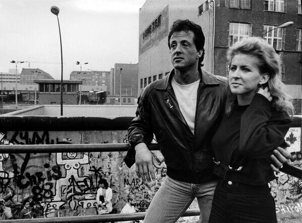 """Звезда """"Рэмбо III"""" Сильвестр Сталлоне побывал у Берлинской стены в 1988 году. На фото он с 22-летней медсестрой из Восточного Берлина Лиан Зундерманн, которая сбежала из Восточного Берлина на Запад, спрятавшись в пассажирском сиденье автомобиля Mini. - Sputnik Беларусь"""