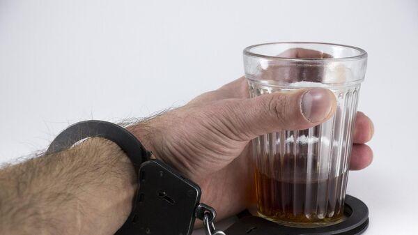 Мужчина в наручниках держит стакан со спиртным, архивное фото - Sputnik Беларусь