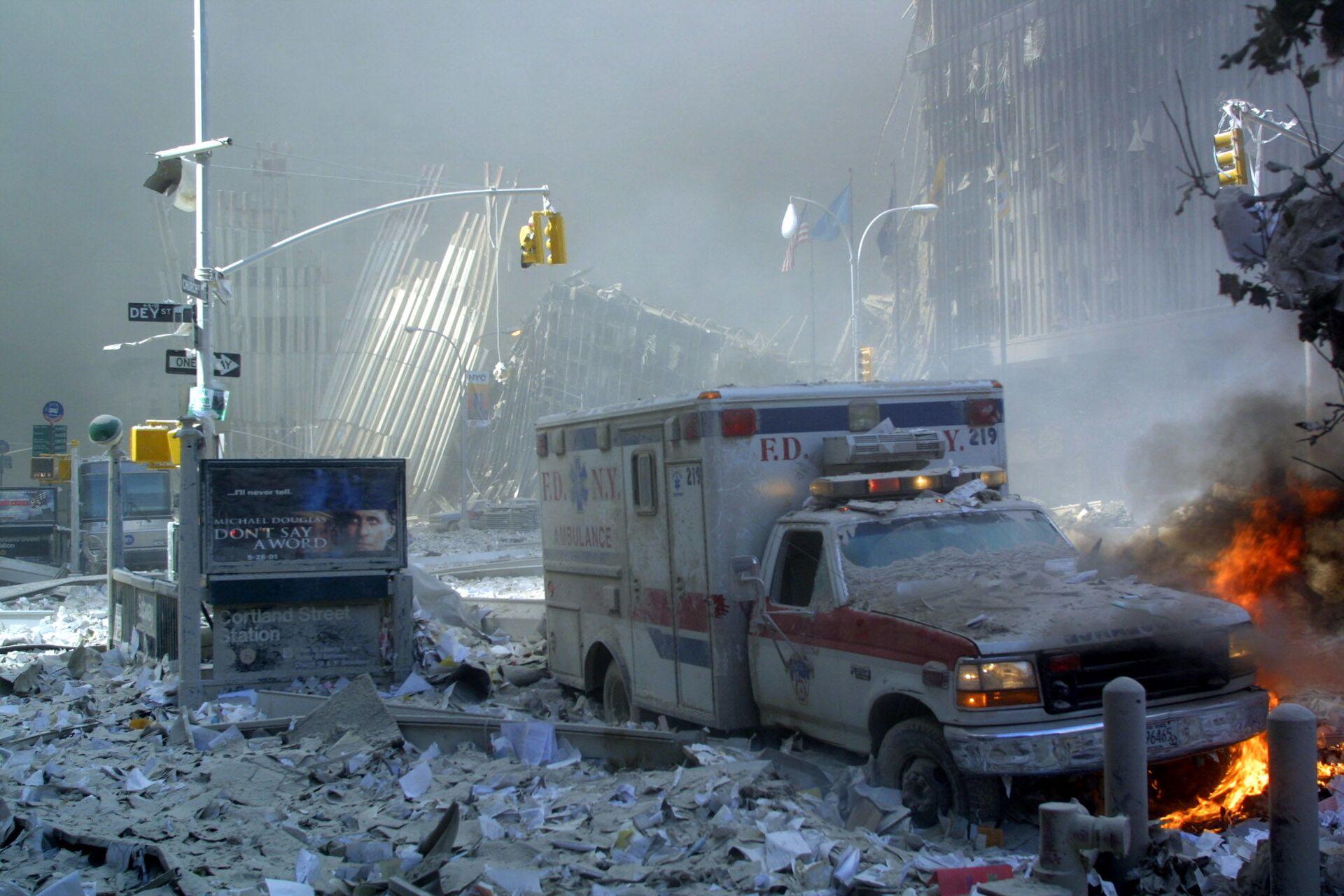 Поврежденный автомобиль скорой помощи и покрытая обломками улица после обрушения первого здания Всемирного торгового центра в Нью-Йорке - Sputnik Беларусь, 1920, 11.09.2021