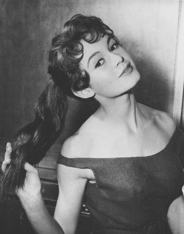 """Французская актриса Брижит Бардо позирует в своем отеле в Лондоне 1 февраля 1955 года. 20-летняя кинозвезда впервые приехала в британскую столицу, где она снималась вместе с Дирком Богардом в фильме """"Доктор на море"""". - Sputnik Беларусь"""