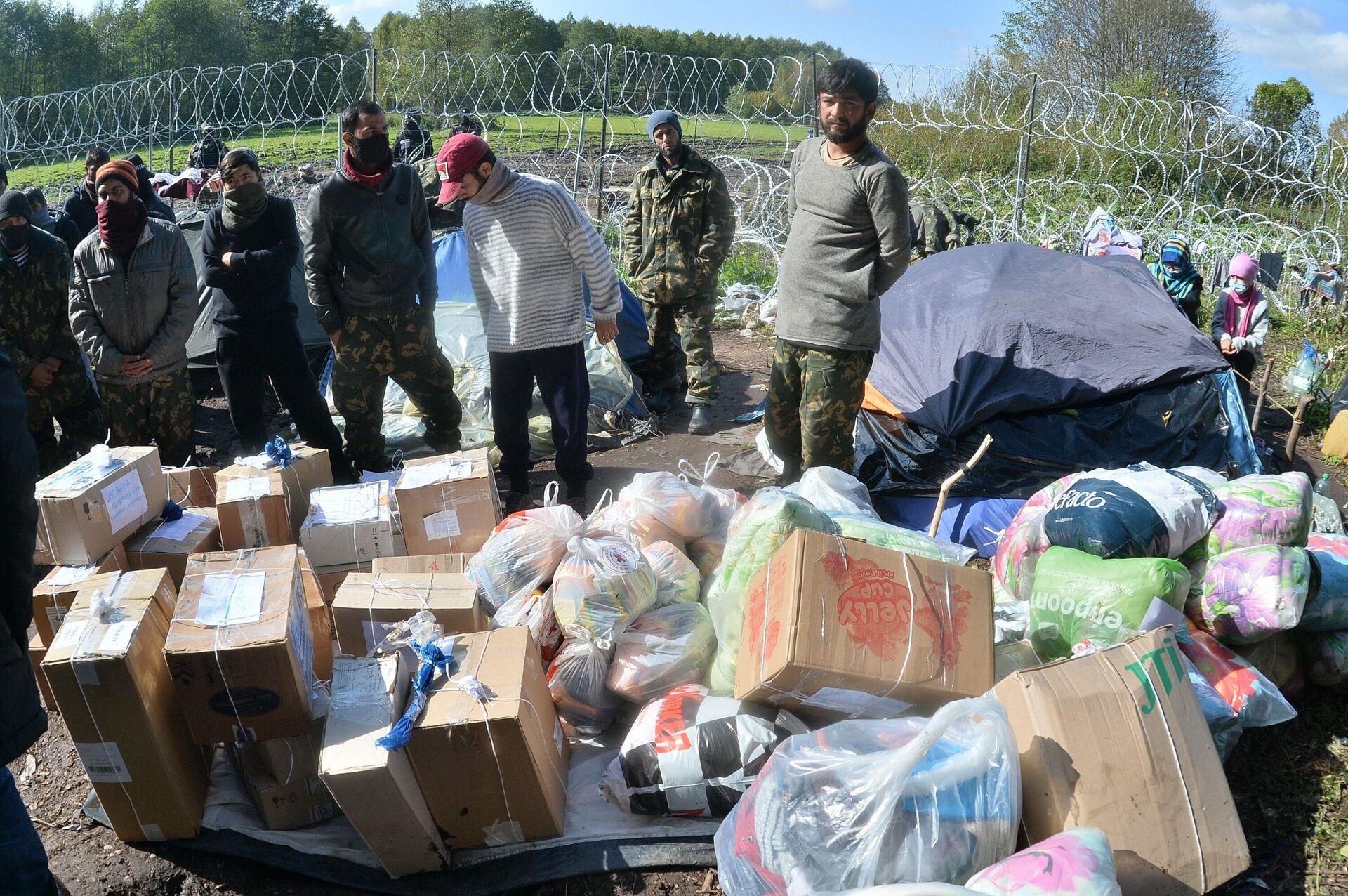 Мигранты периодически получают гуманитарную помощь. Многие из мужчин в военных бушлатах, переданных белорусскими пограничниками с наступлением холодов - Sputnik Беларусь, 1920, 30.09.2021