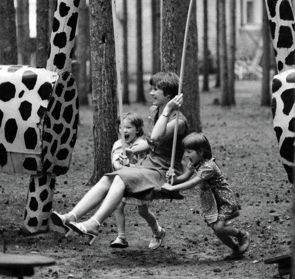 Дзяўчынкі разгойдваюць маму на арэлях ва Ухцінскім дзіцячым парку, 1981 год. - Sputnik Беларусь