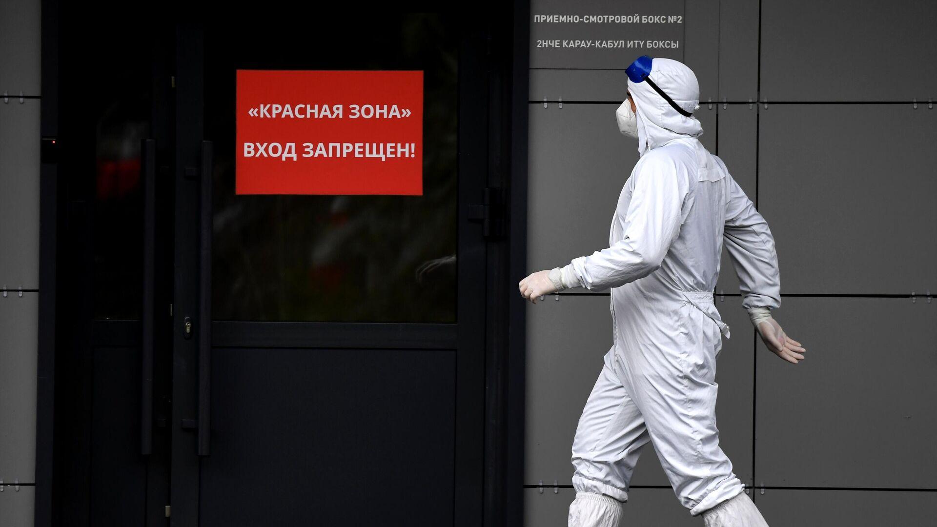 Медицинский сотрудник у входа в красную зону больницы, где ведется прием пациентов с COVID-19 - Sputnik Беларусь, 1920, 13.10.2021