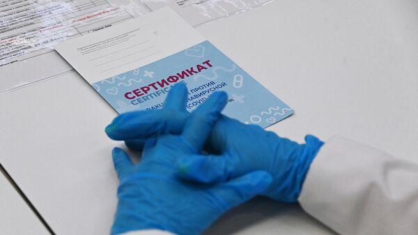Медицинский сотрудник с сертификатом в центре вакцинации от COVID-19 - Sputnik Беларусь