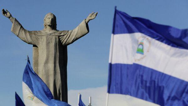 Национальные флаги Никарагуа возле монумента Христу в Манагуа  - Sputnik Беларусь