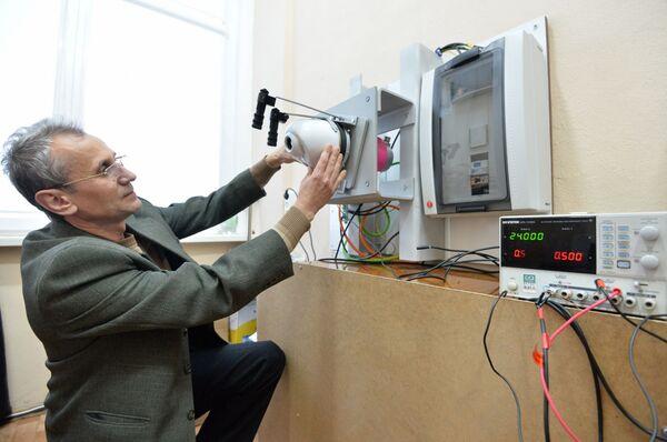 Младший научный сотрудник БАК и технологии Александр Левадный возле образца стенда, который воспроизводит возмущение на действующую видеосистему в полете - Sputnik Беларусь