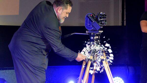 Генеральный директор Беларусьфильм Игорь Поршнев разбивает тарелку о камеру, объявляя об открытии фестиваля - Sputnik Беларусь