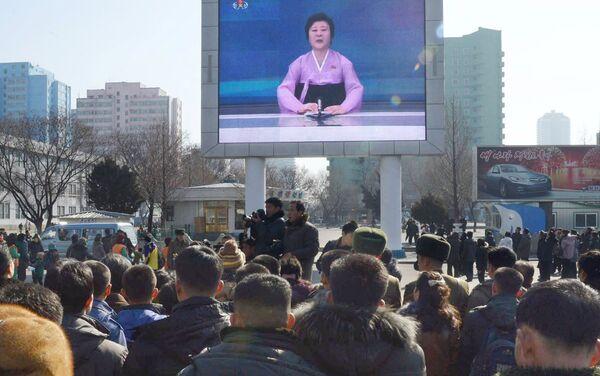 Жители Пхеньяна смотря на экране объявление о запуске ракеты - Sputnik Беларусь