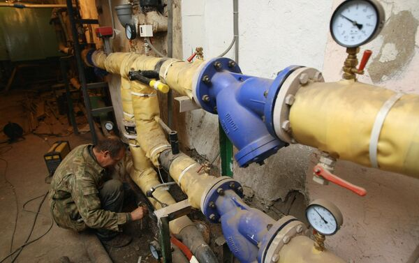 Сантехник красит трубу на тепловом узле в подвале одного из жилых домов. Архивное фото - Sputnik Беларусь