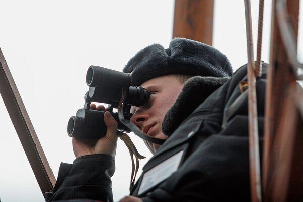 Сотрудник милиции наблюдает в бинокль за обстановкой в зоне. - Sputnik Беларусь