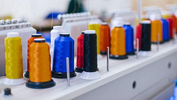 Катушки с нитками на вышивальном оборудовании в швейном цехе, архивное фото - Sputnik Беларусь
