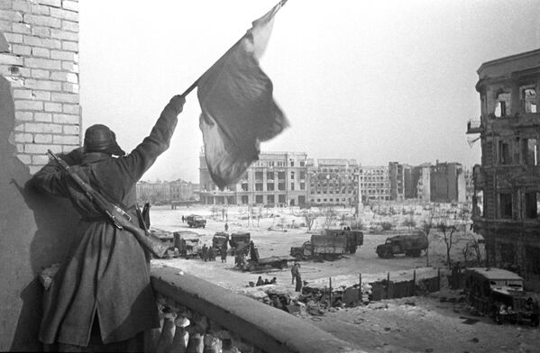 Красный флаг над площадью Павших борцов, освобожденного Сталинграда. На заднем плане — здание универмага, где был взят в плен штаб окруженной 6-й армии вермахта во главе с командующим армией фельдмаршалом Паулюсом. - Sputnik Беларусь