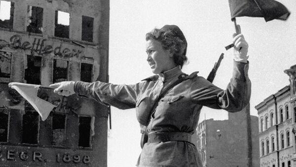 Савецкая рэгуліроўшчыца кіруе рухам транспарту на вуліцы Берліна - Sputnik Беларусь