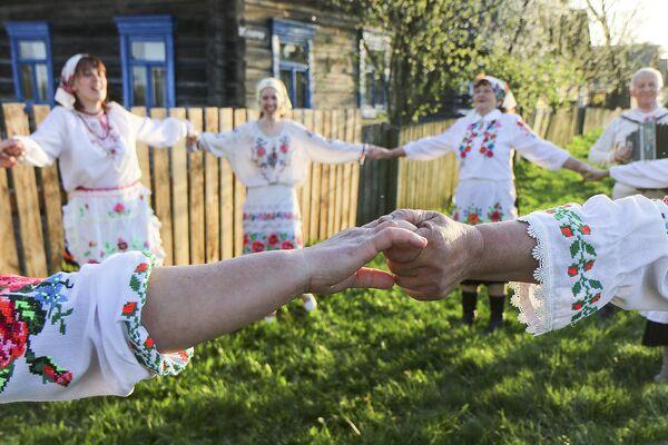 Закопав кусочек хлеба среди всходов, крестьяне берутся за руки и водят хоровод, распевая обрядовые песни.  - Sputnik Беларусь
