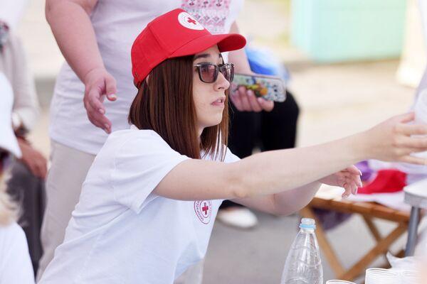 Волонтеры Гомельской областной организации Красного Креста бесплатно раздавали участникам торжеств питьевую воду. - Sputnik Беларусь