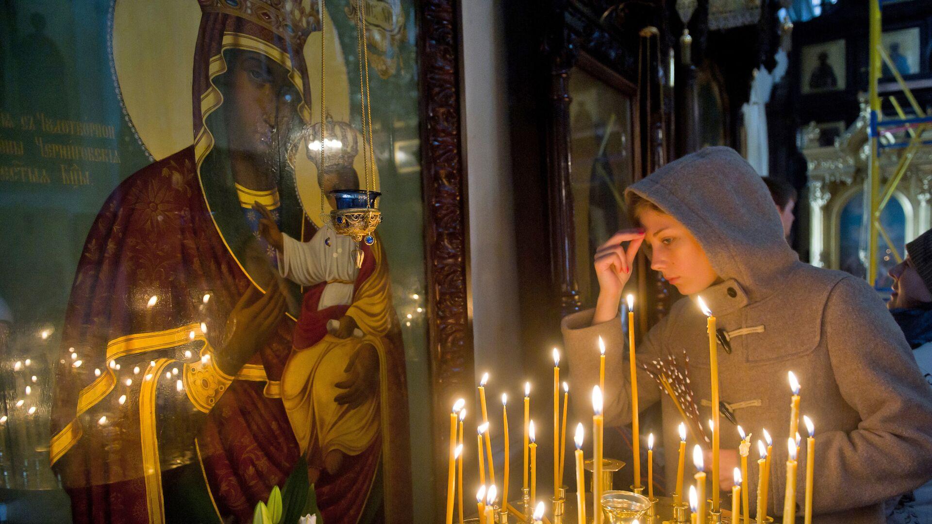 Прихожанка в церкви у иконы Божьей матери - Sputnik Беларусь, 1920, 12.10.2021