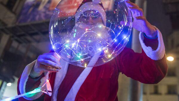 Мужчина в костюме Деда Мороза во время празднования Нового года в Санкт-Петербурге - Sputnik Беларусь