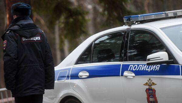 Сотрудник полиции возле служебного автомобиля, архивное фото - Sputnik Беларусь