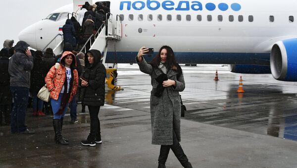 Дзяўчына фатаграфуецца на фоне новага самалёта Boeing 737-800 авіякампаніі Пабеда - Sputnik Беларусь