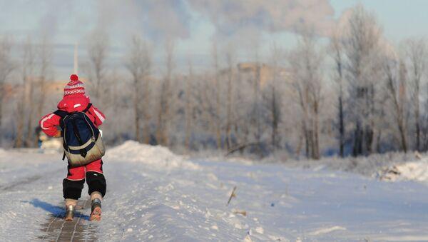Школьник идет по заснеженной аллее - Sputnik Беларусь
