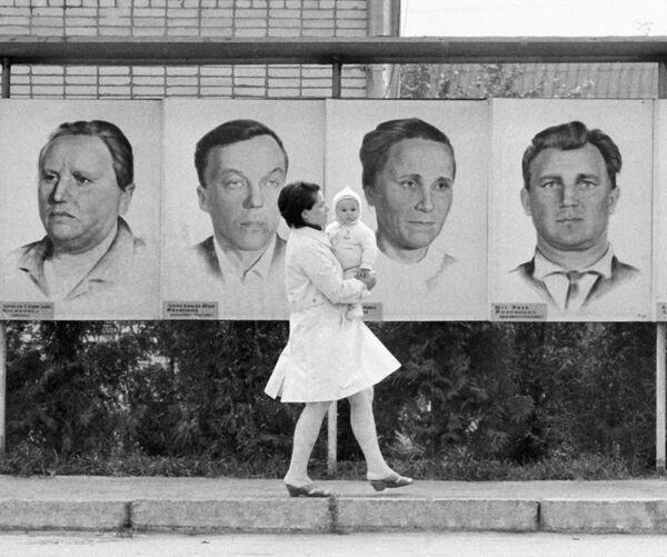 Женщина с ребенком на фоне портретов героев труда, БССР, 1970 год. - Sputnik Беларусь